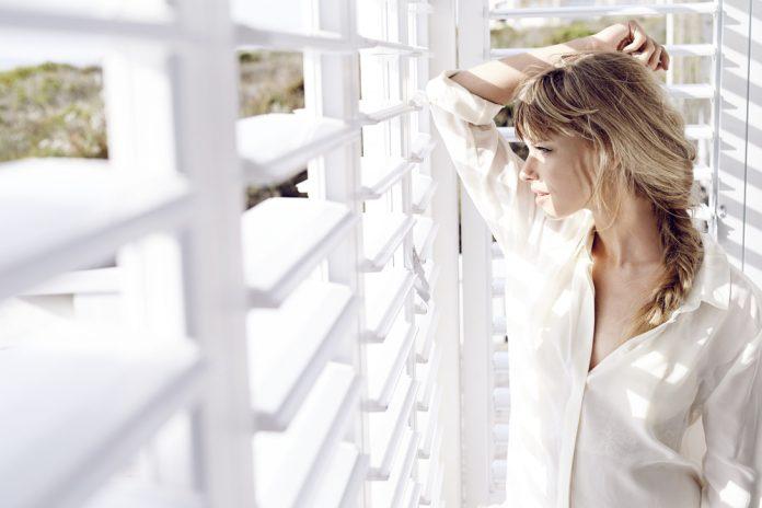 vrouw kijkt door shutters heen